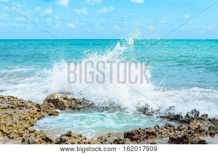 Ocean Water Splashing On Rocks And Forming A Natural Pool In The Center Of The Image. Sunny Day, Ver
