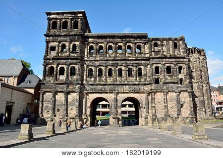 Trier, Germany - April 26, 2016. 2nd-century Roman city gate Porta Nigra in Trier, with surrounding buildings and people.