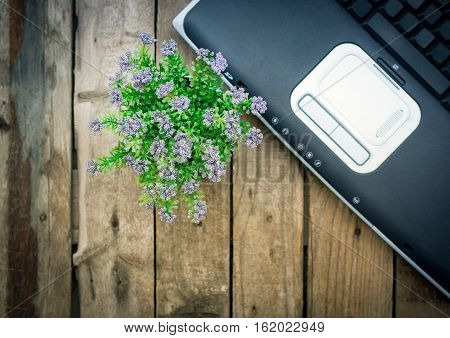 Laptop With Touchpad And Flower On Wooden Background