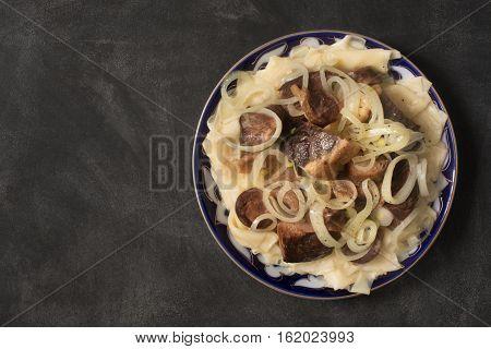 National Kazakh dish - Beshbarmak prepared with meat and pasta on the dark chalkboard