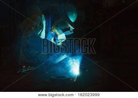 Welder of Metal Welding with sparks and smoke in steel industry