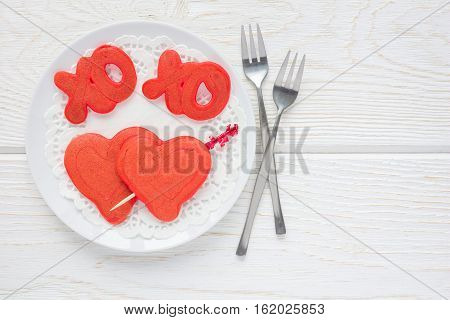 Red velvet pancakes with xo sign (hugs and kisses) and heart on white plate horizontal top view copy space