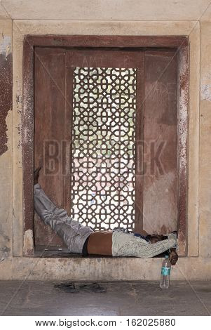 Fatehpur Sikri, India - October 12, 2016: Tired man sleeps on a lattice window during daytime at Jodha Bais Palace in Fatehpur Sikri, Agra, India.