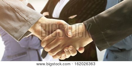 handshake of business partners on background of office