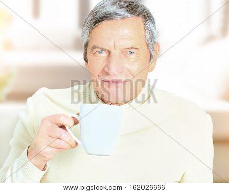 Portrait of senior man holding coffee mug smiling at camera
