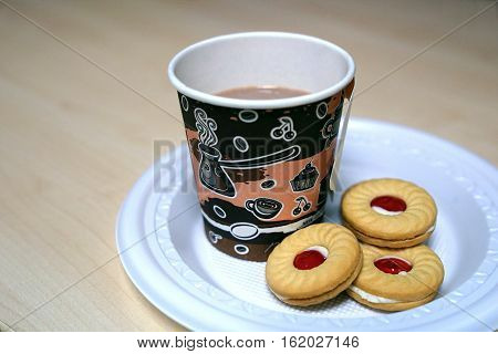 Paper cup of coffee and sandwich cookies with strawberry jam in plastic plate on wooden table