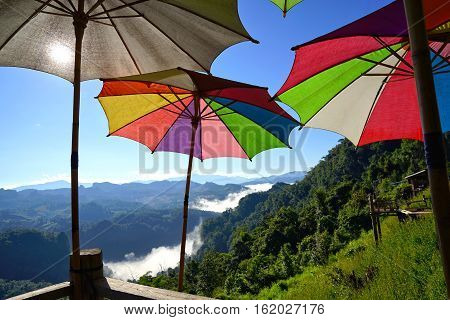 Morning mountain landscape with waves of fog and multicolor big umbrella at baan ja bo Mae Hong Son Northern Thailand. Waves of clouds in the background peaks covered with coniferous deciduous forests