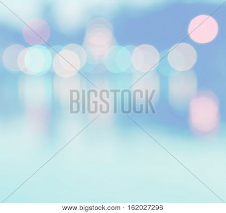Abstract multicolor blurred bokeh light with water reflection on blue background