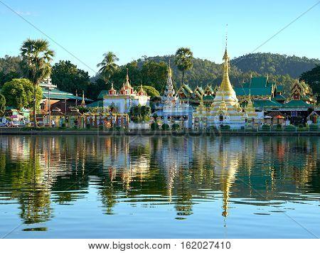 Golden pagoda of Wat Chong Klang and Wat Chong Kham with reflection Burmese Architectural Style temple Mae Hong Son Northern Thailand