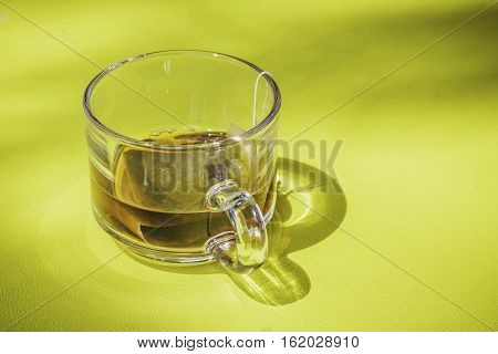 Closeup of teabag on cup and on table.