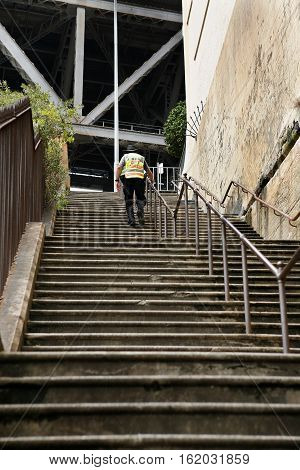Sydney Australia-January 31 2017. Male City Ranger climbs steps in the historic Rocks area of Sydney just below the Sydney Harbour Bridge. City Rangers regulate on-street parking and provide assistnace to members of the public on the streets of Sydney New
