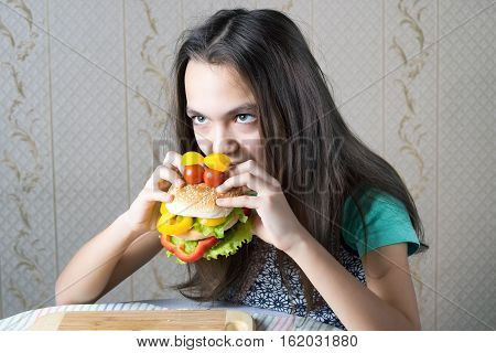 11 year old girl bites her teeth into a burger made in the form of faces with eyes of cherry tomatoes.