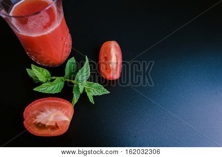 glass of tomato juice, tomatoes and leaves on a dark background