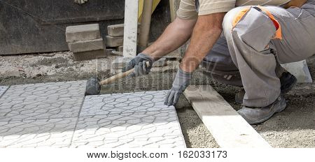 picture of a Worker tapping pavers into place with rubber mallet.