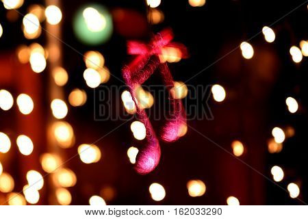 picture of a cristmas music note decoration in front of a bokeh lights movement blurr