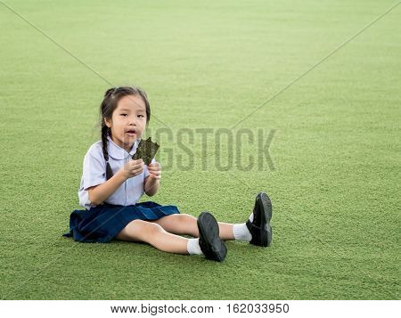 Happy Asian Child Eating Delicious Nori Seaweed, In The Garden
