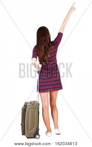 Back view of  pointing woman with suitcase looking up. Standing young girl. Rear view people collection.  Pretty girl in a striped dress stands with a suitcase and looking at something