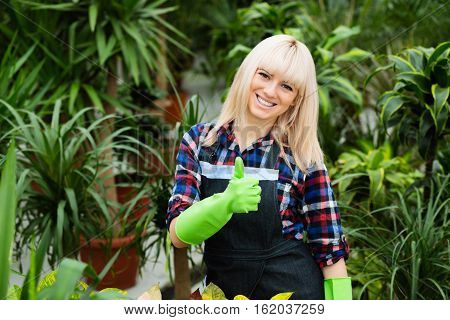 Portrait cheerful woman gardener wearing protective gloves showing thumbs up. standing in a garden center
