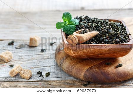 Oolong Tea And Green Mint In A Wooden Bowl.
