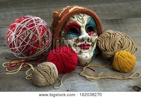 yarn and mask in a cap on a wooden table