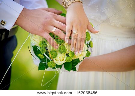 Couple put their hands on a bridal bouquet. Beautiful wedding bouquet. Hands newlyweds with rings.