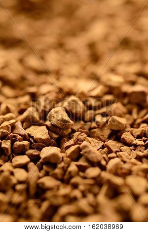 Granules of instant coffee background. Selective focus
