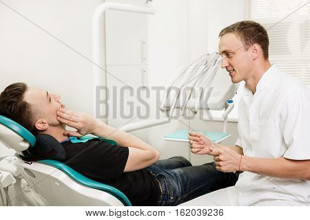 Male dentist talking to patient who sitting in the dental chair and complains of toothache. dental clinic office