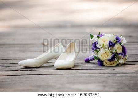 Bride Shoes and bridal bouquet lying on the wooden bridge. Fashion beautiful bride's shoes standing on the wooden floor. Bridal bouquet lying on the wooden boards.