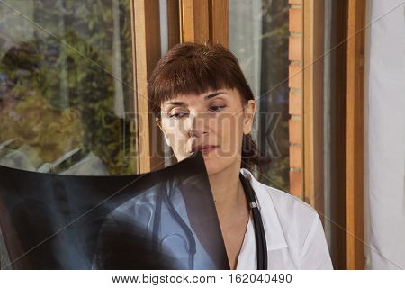 doctor examines a radiograph near a window