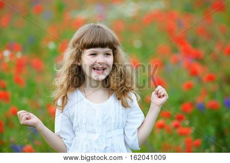 happy and smiling little girl portrait with clenched fists outdoors