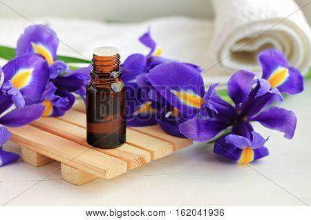 Aroma oil dropper bottle, bright fresh blue flowers, towel. Botanical beauty treatment.