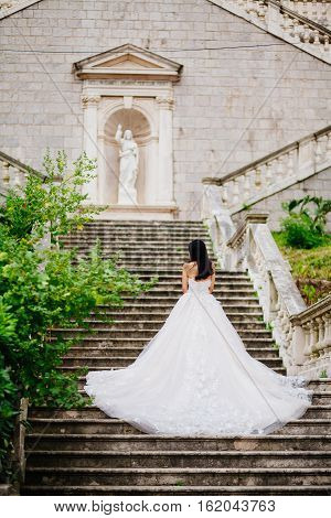 bride in wedding dress with church background. Back view. Destination wedding