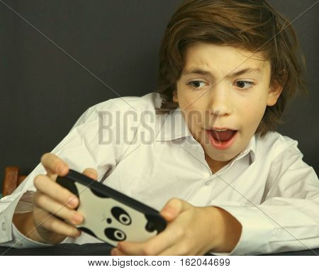 Boy Play Computer Game On His Cell Phone