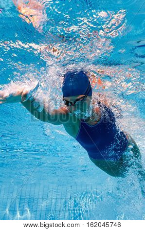 Front crawl swimmer from beneath, toned image, vertical image