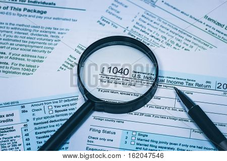 1040 Individual Income Tax Return Form with pen and magnifying glass up detailed close up. Concept for personal individual financial citizen responsibility and awareness.