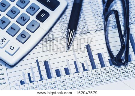 Accounting financial bank banking banker account stock spreadsheet data with glasses pen and calculator in blue financial concept analysis calculations review concept
