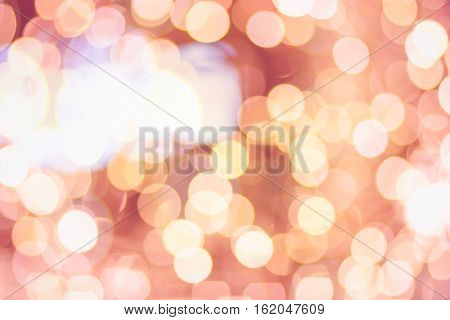 Christmas New Year bokeh background. Blurred light in warm tone background. Store shop mall concept. soft focus dream city blurry rich pink, orange and golden bubble light wallpaper