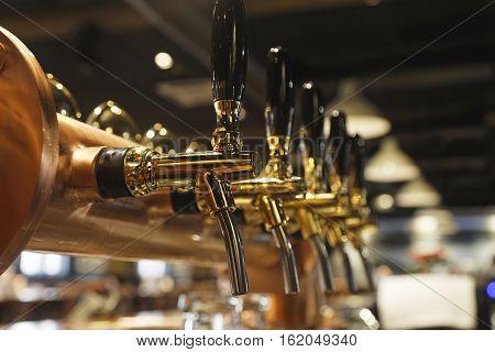 golden shiny beer taps in beer bar