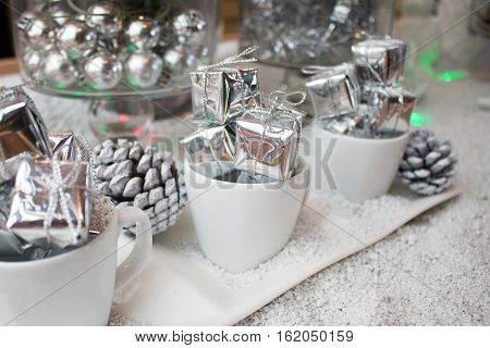 Silver Christmas Gifts Box In Coffee Cup Decorate With Snow For Christmas New Year.
