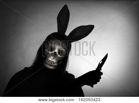 Silhouette of spooky robber or grim reaper with knife in rabbit costume.  Violence and criminality concept. A bloody Easter in the slum.