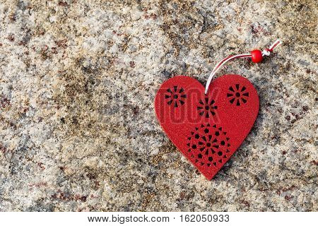 Red wooden heart decoration on stone background. Love concept.