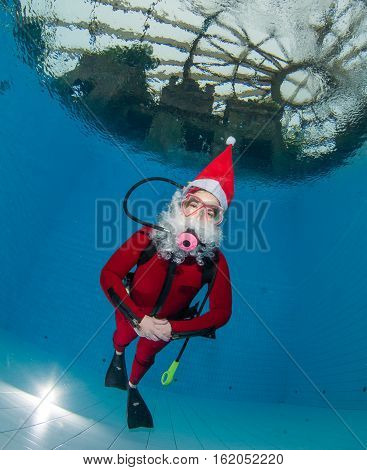 Scuba diving in Santa Claus costume in a pool