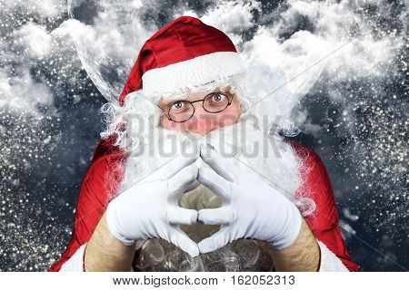 Santa Claus In The Christmas Night , With Sky Full Of Stars, Snow, Clouds And The Moon In The Backgr