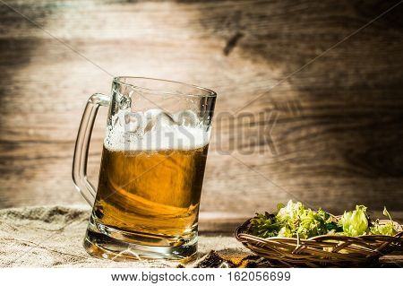 Big mug of beer standing on empty wooden background with hops on table