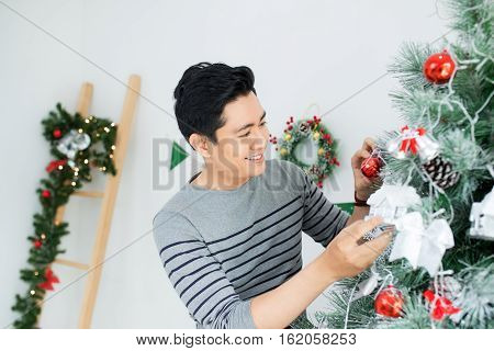 Christmas. Asian Handsome Man Standing New Xmas Tree At Home Celebrating New Year.