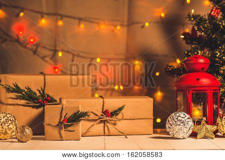 christmas tree light and gift boxes on wooden table.