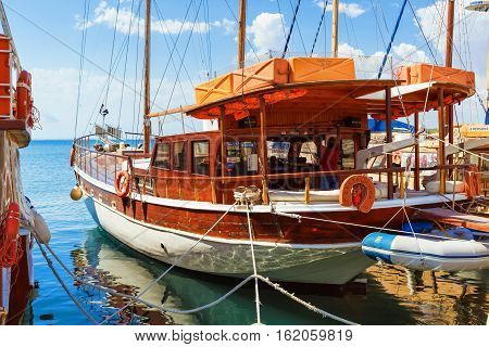 Nesebar Bulgaria - September 06 2013: Wooden passenger pleasure ship standing at the pier in the port of the old town of Nessebar on the Black Sea coast. Sunny summer day.
