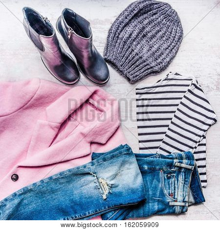Collage of autumn-winter female clothing set. Pink coat blue ripped jeans sriped blouse knitted hat and black leather boots over white wood background. Modern urban style outfit.