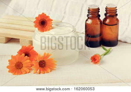 Calendula anti-acne facial mask. Jar of white cream, bright marigold fresh flowers, essential oil bottles. Homemade healing cosmetics. Toned.