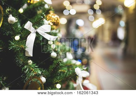 Christmas pine tree with decorations in trading hall. Toned photo